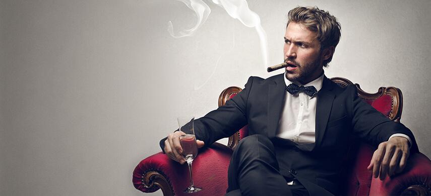 gut aussehender Mann sitzt im Sessel und raucht